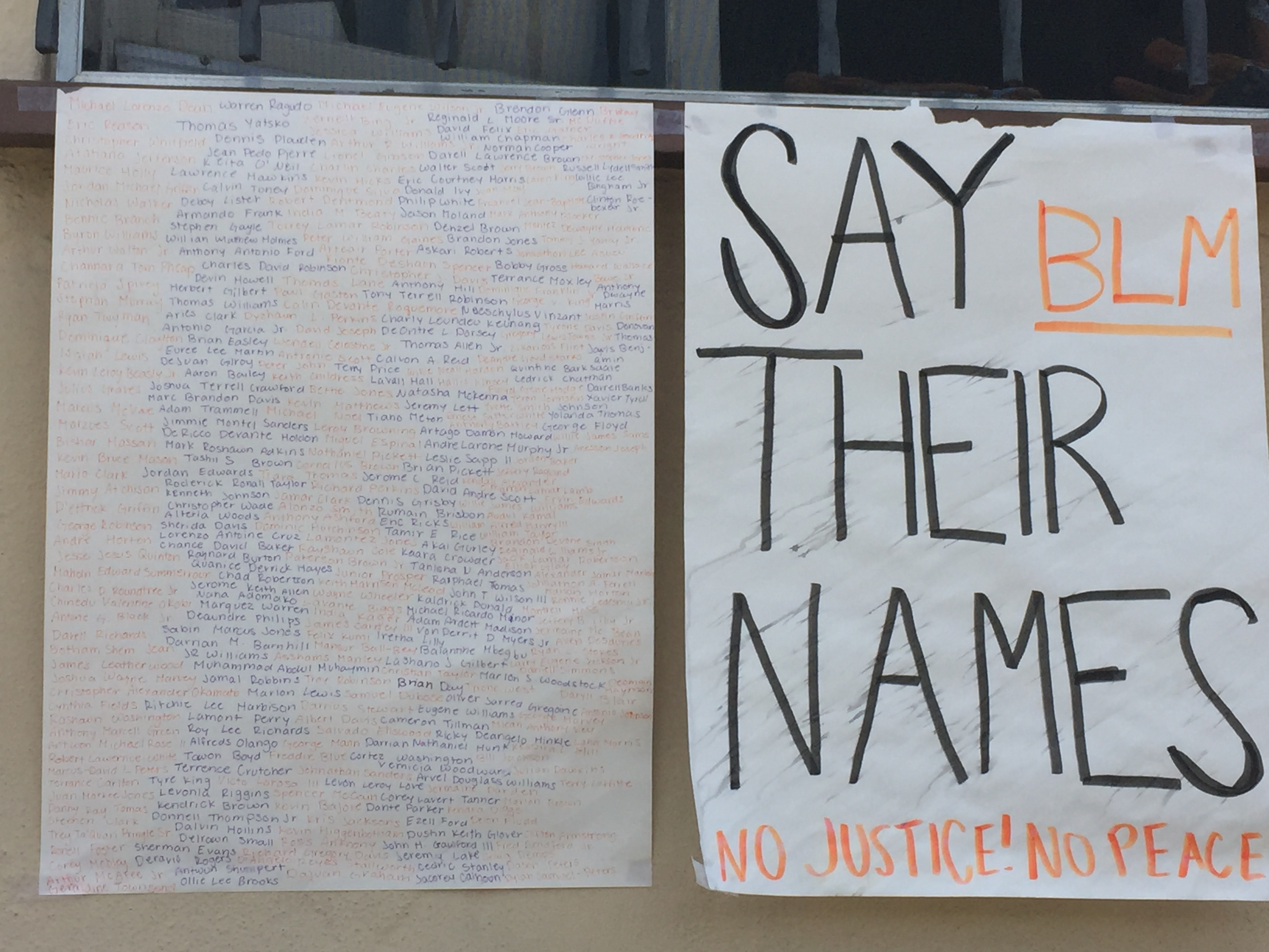 "Posters displaying the name of Black people killed by police telling readers to ""Say their names"" and ""No justice! No peace!"""